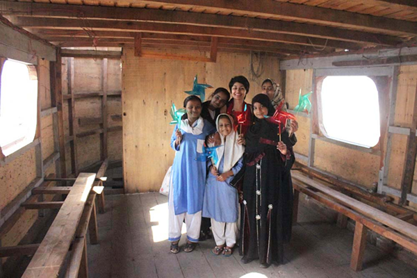 Pin wheel project, posing with students inside the Indian boat