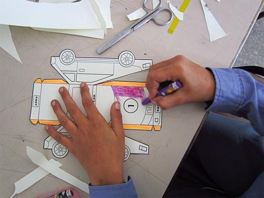 2D and 3D activity, student coloring a 2d print of a car