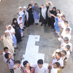 Drawing the map, top view of teacher and students encircling the drawing assemblage